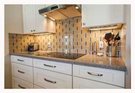 Phoenix AZ Open Concept galley kitchen with white cabinets and gray quartz countertops.