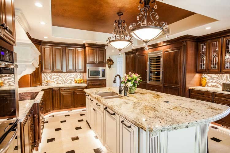 Gilbert, AZ kitchen remodeling contractor. Upscale  kitchen remodel with two tones of wood cabinets, a large island, a stone cook-top hood and LED lighting.