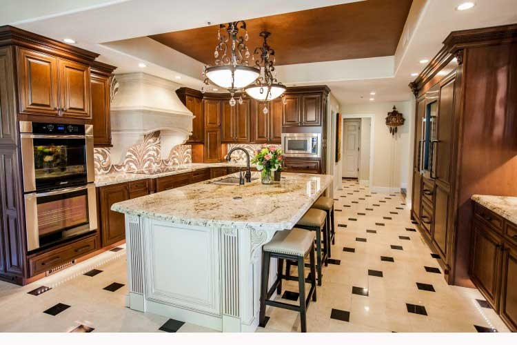Award winning Scottsdale Kitchen Transformation. Upscale Scottsdale kitchen remodel with rich custom cabinets, a large center island, a stone cook-top hood and LED lighting.