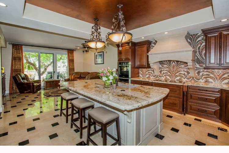 Kitchen Remodeling Contractor in Chandler, AZ. Luxurious kitchen renovation with two tones on wood cabinets, a large island, a stone cook-top hood and LED lighting.