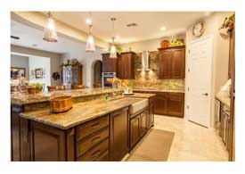 Open Concept kitchen with dark wood cabinets granite counters and island seating in Phoenix AZ.