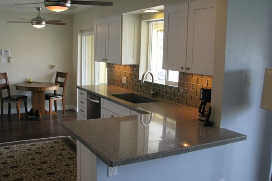 Kitchen Remodeling Contractor in Phoenix, AZ. Open concept galley kitchen renovation with gray quartz counter tops and white cabinets.